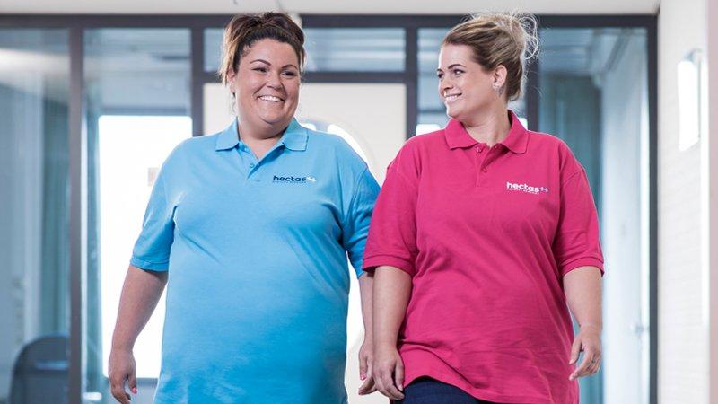 Unternehmenswerte - Zwei Kolleginnen laufen Flur entlang