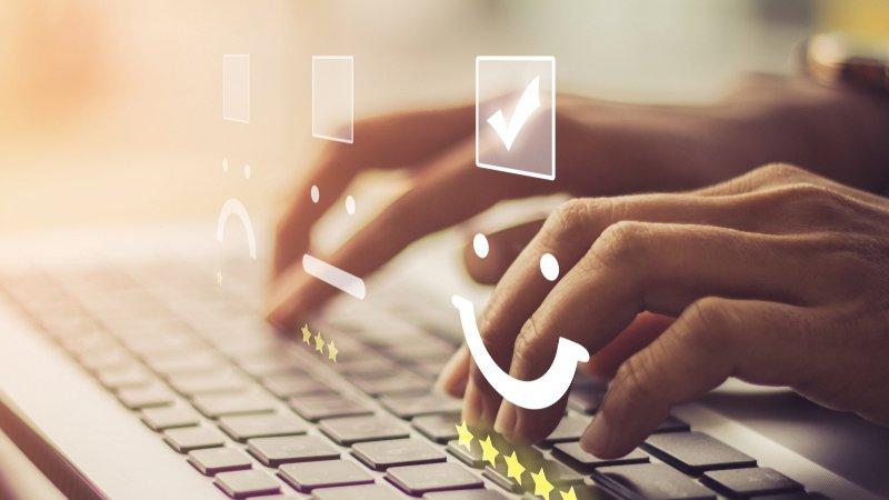 Geschäftsfrau drückt Zufriedenheitsemoticons auf Tastatur, um hectas Kundenbefragung 2019 auszufüllen.