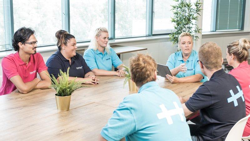 Nachhaltiges Handeln - Mitarbeiter sitzen zur großen Teambesprechung zusammen