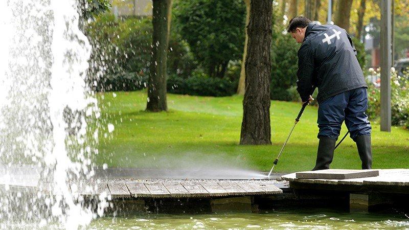 Grünpflege - Reinigungskraft reinigt Außengelände mit Hochdruck