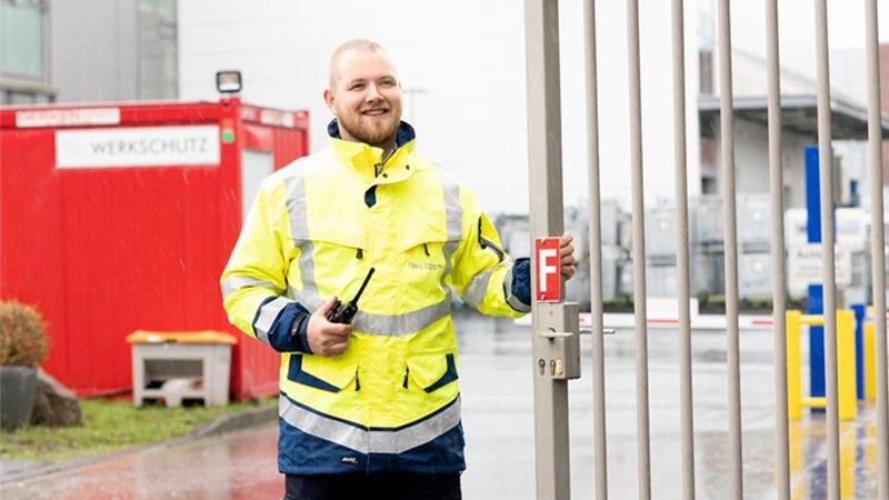 Automotive - Sicherheitskraft bewacht Zufahrt von Werksgelände