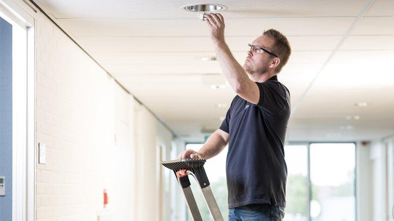 Gebäudedienste - Hausmeister wechselt Leuchtmittel aus