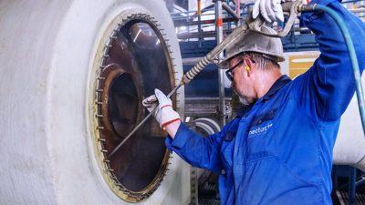 Unternehmenswerte - Reinigungskraft reinigt Industriemaschine mit Hochdruck