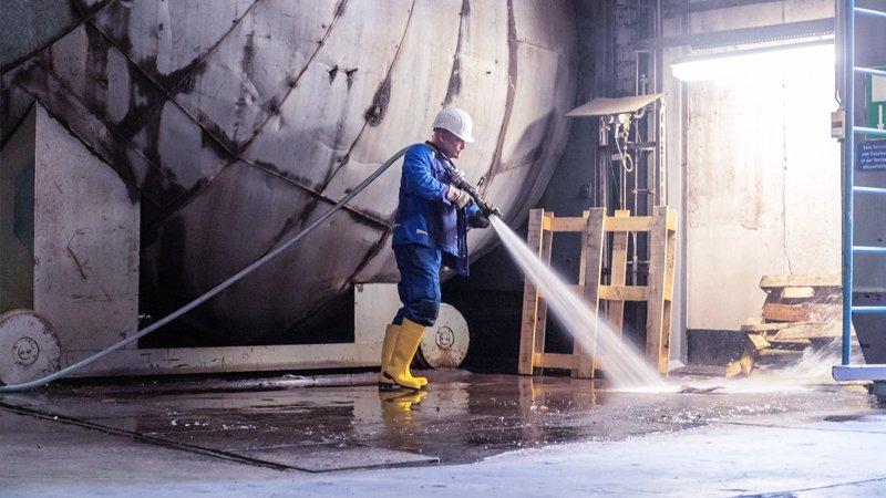 Reinigungskraft reinigt Industrieboden mit Hochdruck