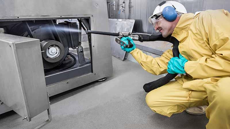 Industrie - Reinigungskraft reinigt Maschine mit Hochdruck