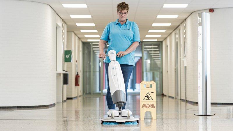 Reinigungskräft reinigt Boden mit Maschine.