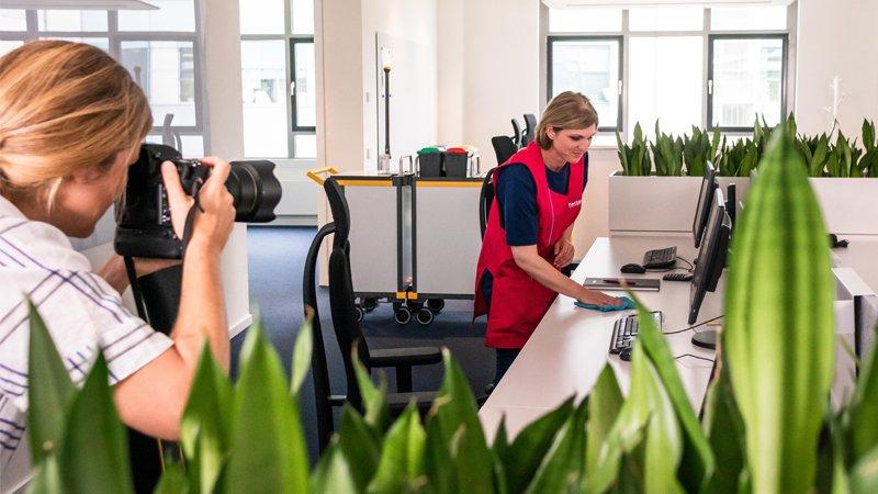 Fotoshooting von hectas. Fotografin fotografiert hectas Reinigungskraft beim Tisch abwischen.