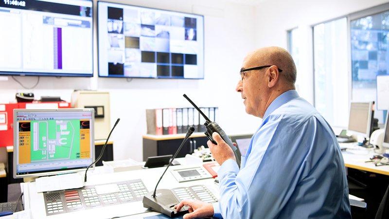 Sicherheitskraft mit Funkgerät und Monitoren